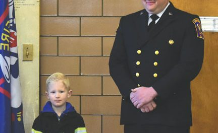 NEPHEW HOLDS BIBLE FOR UNCLE AS HE IS SWORN IN AS DEPUTY CHIEF